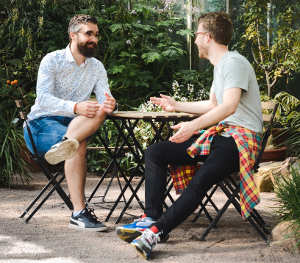 two men chatting at table
