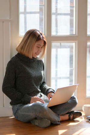 woman with laptop in front of window
