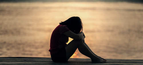 woman looking sad in front of lake