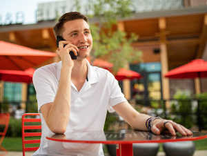 young man talking on phone at table